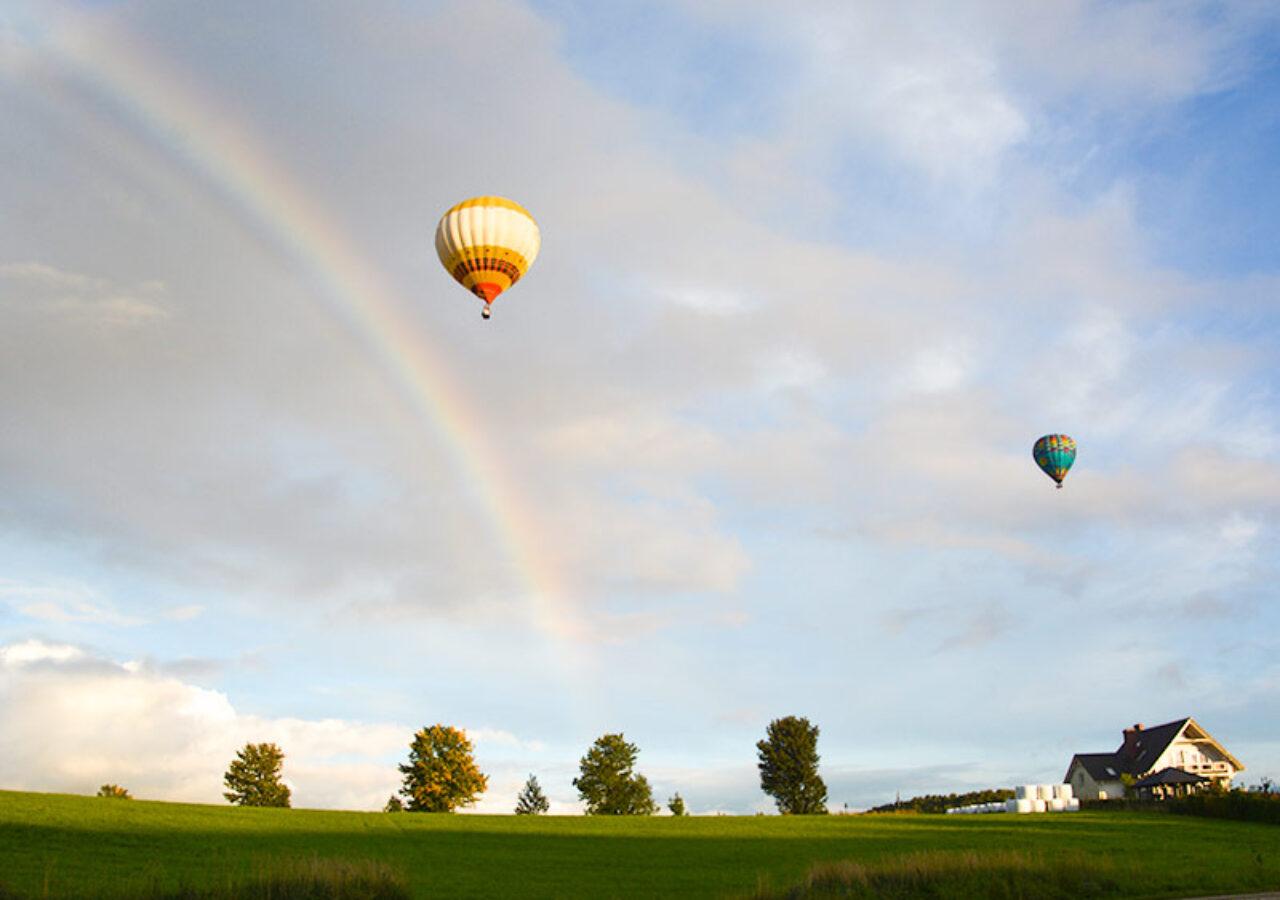 Lot balonem podczas eventu integracyjnego z tęczą w tle